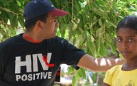 Man wearing an 'HIV Positive' shirt standing next to a girl