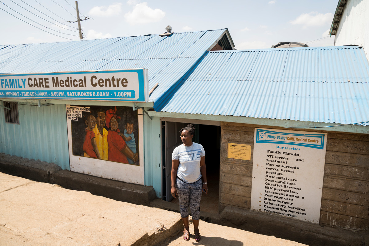Community Health Volunteer Mary Mukuni, stands for a portrait outside of the Family Care Medical Centre (FHOK) in Kibera, Nairobi, Kenya