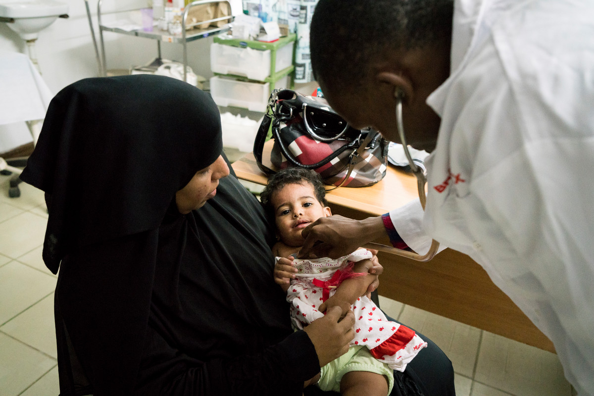 Clinical Officer Adillahi Ali,  checks baby Fatma as she sits with her mother Anisa, at The Family Care Medical Centre (FHOK) in Malindi, Kenya