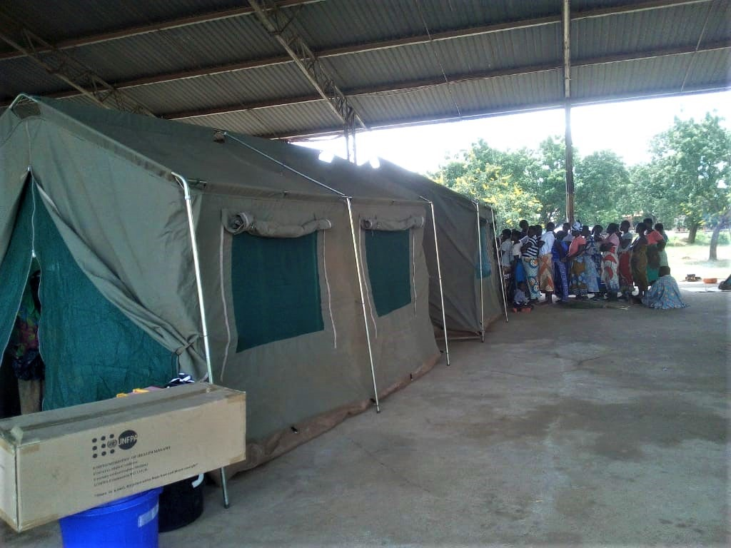Clients queuing up for SRH Services at Bangula Evacuation Camp. Inside the shelter are FPAM tents.