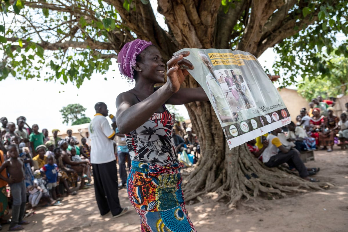 A woman shows one of the posters to the villagers during the ATBEF event in which the staff will talk about contraception and family planning in Ilama, Togo.