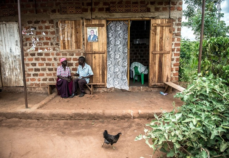 John Owoli, a VODA-supported community volunteer, counsellor and catechist, speaks with a client at his home near Kasawo, Uganda.