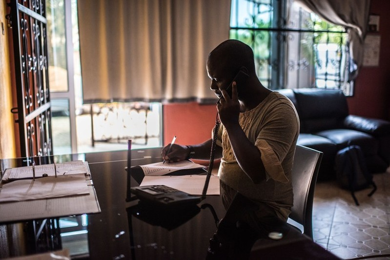 Ali Kikongo, a program officer with Little Mermaids Bureau, takes a call on the sex-workers hotline at the LMB office in Kampala, Uganda.