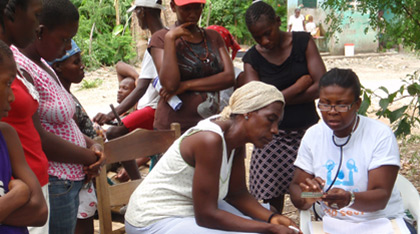 An staff member explains the contraceptive pill to a woman while girls watch