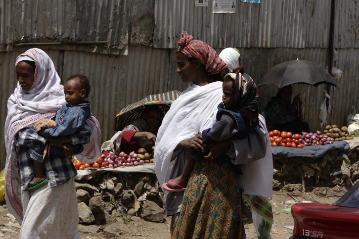 two women walking and holding babies in Ethiopia