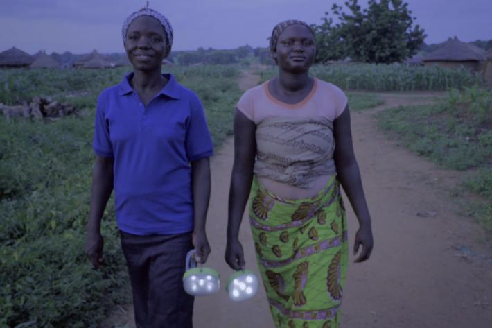 Two Ghanaian women carry torches in the dark