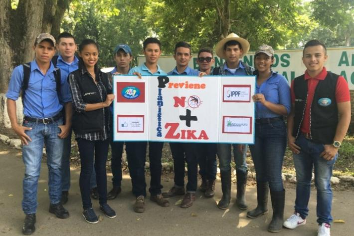 Youth volunteers from IPPF clinic in Honduras hold a banner about Zika