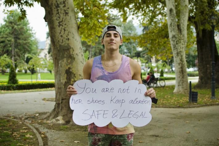 "Boy holding a sign ""Keep abortion safe and legal""."