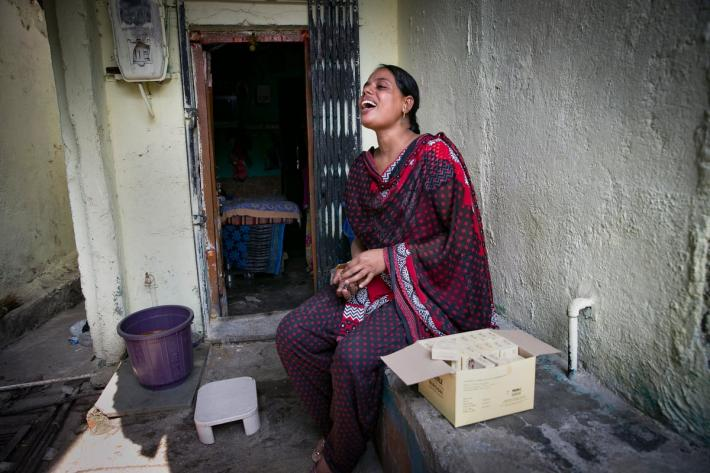 Hasina, a sex worker and peer educator sits outside a brothel, India