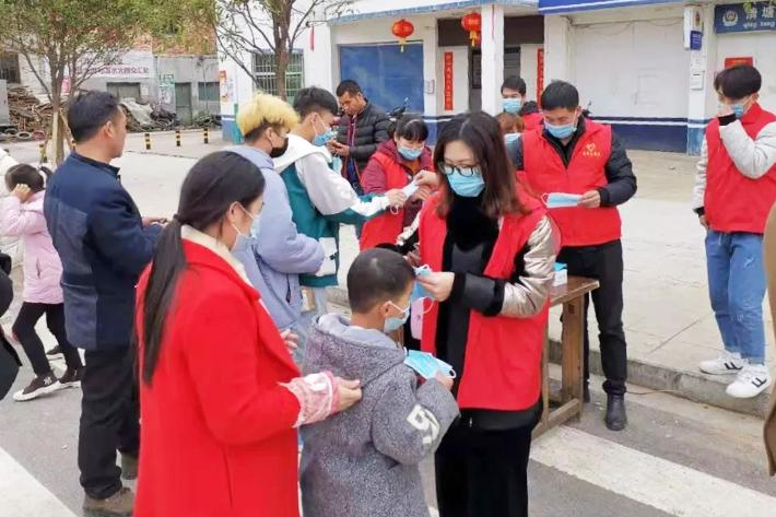China Family Planning Association representatives showing people in the community how to wear masks correctly