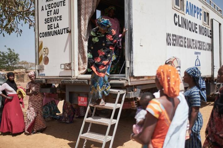 A woman exits the AMPPF mobile clinic