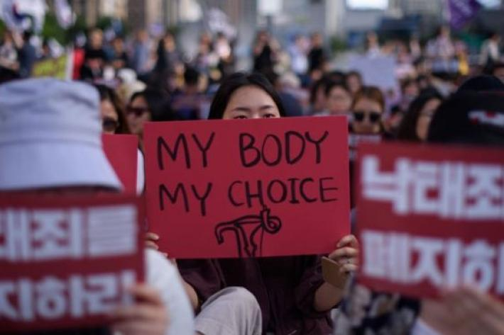 a woman holds a sign saying my body, my choice