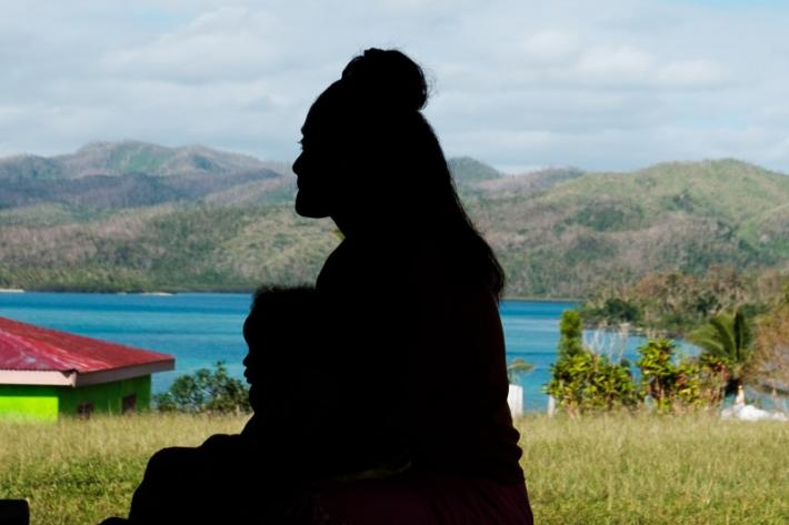 A silhouette of a woman and young child in Fiji