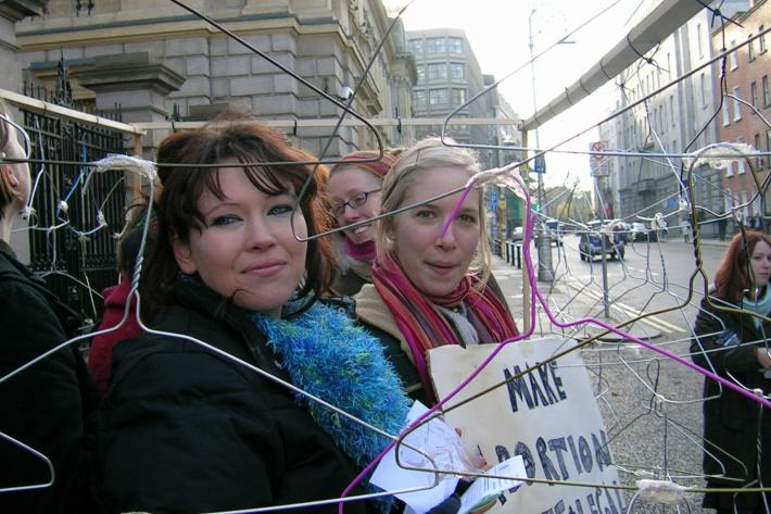 women holding coat hangers to protest against abortion law