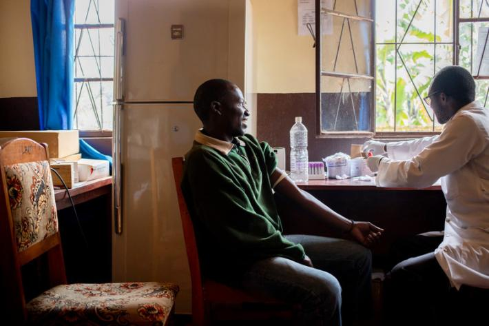 Justin, 41, sits for a blood test by lab specialist Maurice, 33, at ABUBEF's clinic in Ngozi. Due to budget cuts Maurice now works part time; he also works at the local public hospital. Lost funds also mean less reagents available for his equipment making some tests impossible to continue.