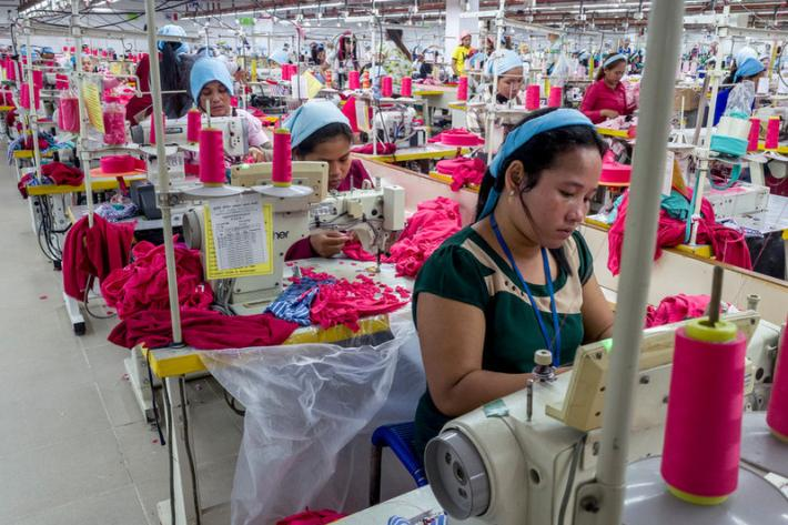 A group of garment workers work on the production line inside the Propitious garment factory in Krong Ta Khmau city. The factory employs more than 3,500 workers and specializes in children's clothes, but also produces a variety of men and women's clothes. The factory has seen a rise in productivity and a reduction in staff taking sick days since RHACs' health outreach programme has been introduced.
