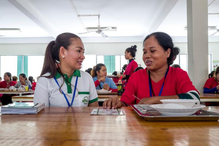 RHAC hotline counsellor, Ing Samnang, speaks to a garment worker during her lunch break inside the canteen of the Dewhirst Garment Factory.