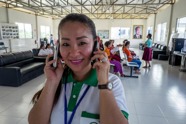 "Ing Samnang's is constantly juggling mobile phones. ""I take 30 calls a day on average,"" she says. Samnang is RHAC's only hotline counsellor. ""I feel good when I help people solve their problems."""