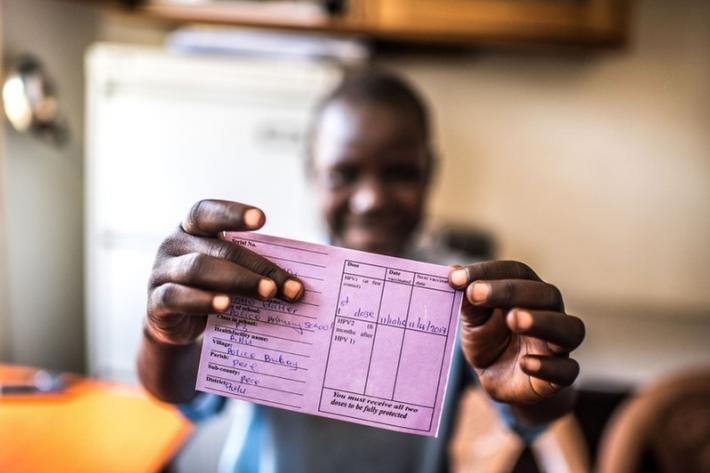 Aciro proudly displays her HPV vaccination card at the RHU clinic in Gulu in Uganda.