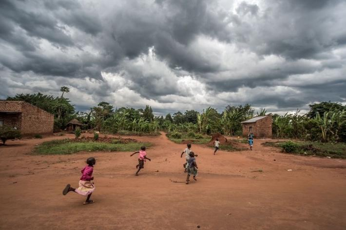 Children run through a village in Kasawo, Uganda, as a storm approaches.