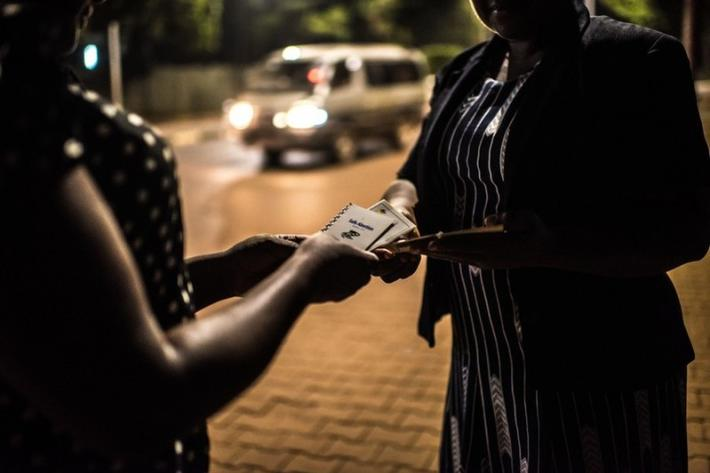 Deborah, a sex worker and beneficiary of the Lady Mermaid's Bureau project, receives a booklet on safe abortion from LMB project officer Noor in central Kampala.
