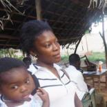 Dié G. Estelle carrying her daughter, born at an internally displaced people camp, talking with an AIEBF coordinator.