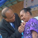 Norma Yeeting receiving her award from President Taneti Mamau