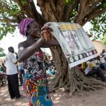 volunteer holds a family planning poster, Togo