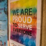 a poster in a clinic stating 'we are proud to serve everyone'