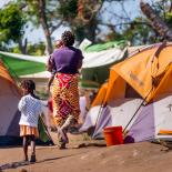 A woman walks through a makeshift camp with her two children after cyclone Idai in Mozambique