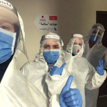 Healthcare workers in PPE giving a thumbs up