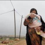 Palestinian mother carrying her child